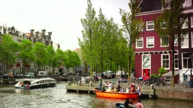 AMSTERDAM, THE NETHERLANDS: ULTRA HD 4k, Real time; Boats sail in Amsterdam canal in Amsterdam. The 17th-century canal ring area is on the UNESCO World Heritage List. — Stock Video