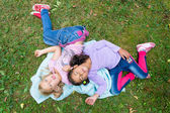 Två barn flickor låg i trädgården leende — Stockfoto
