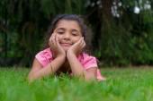 Små zigenska barn flicka låg i gräset med huvudet i händerna — Stockfoto