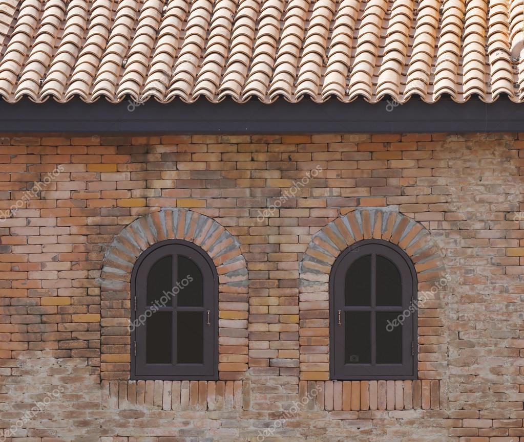 Finestra ad arco in legno verniciato marrone scuro in un muro di ...