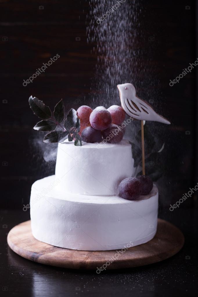 bolo de duas camadas de branco decorado com uvas um pssaro e deixa em um fundo