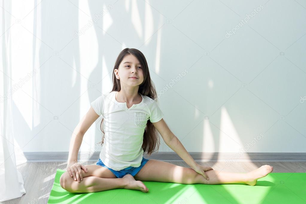 Little Girl Doing Gymnastics On A Green Yoga Mat Doing