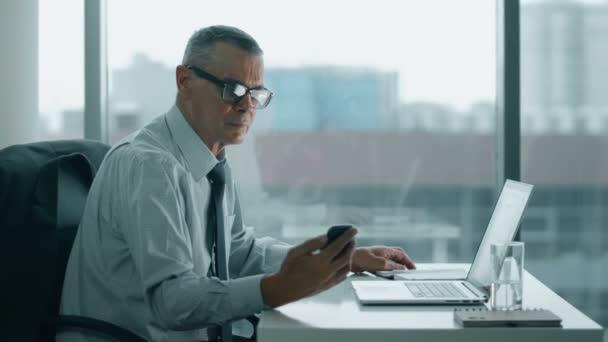 Empresario de edad avanzada ver tel fono y trabajo con la for Ver videos porno en la oficina