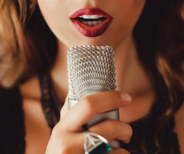 Beautiful girl singing into  microphone