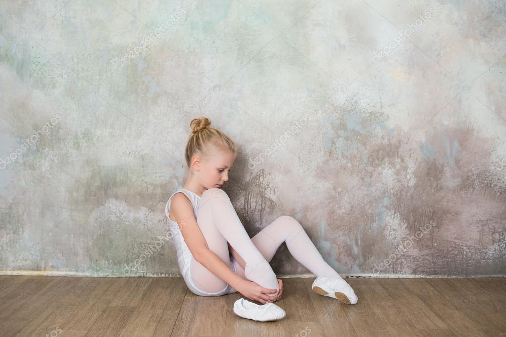 Kleines Ballett-Tänzerin Dehnen vor der Klasse im weißen Badeanzug ...