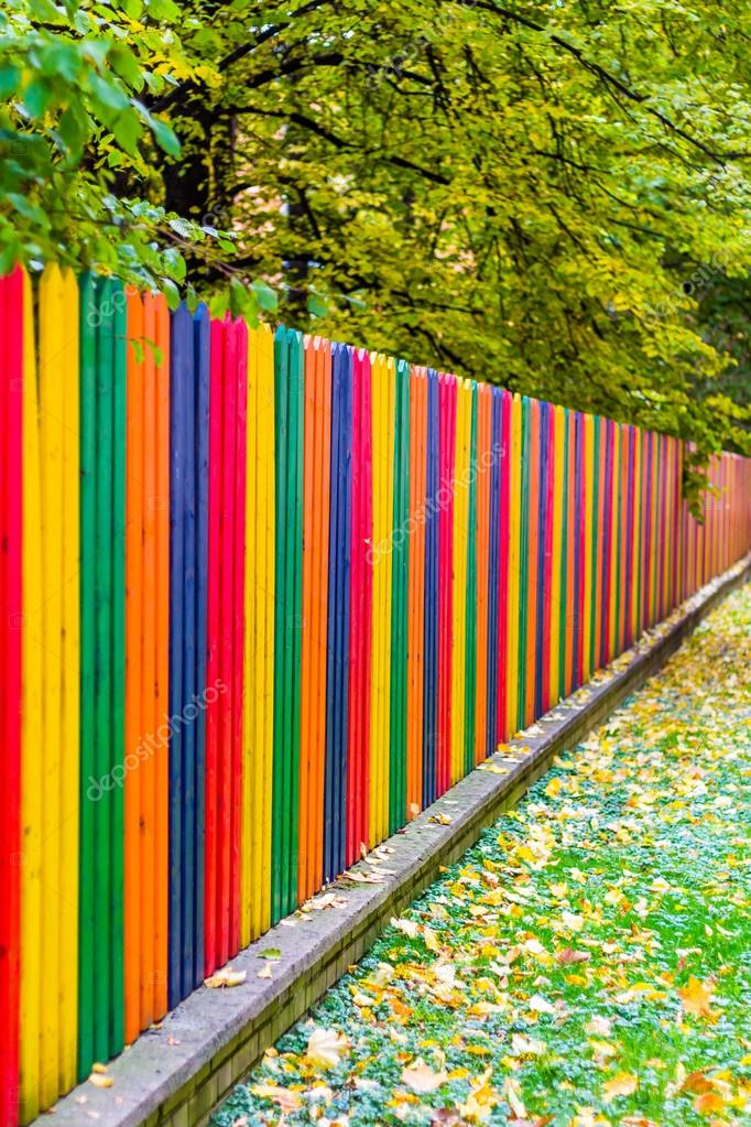 Multi colored rainbow wooden fence in autumn — stock photo