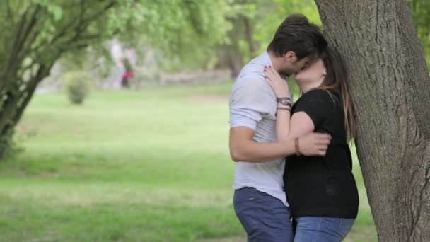 Two young people kissing in a public park under a tree ...