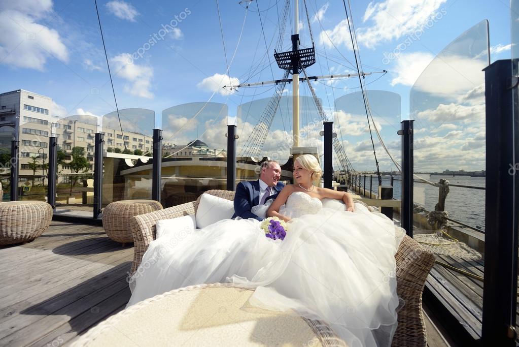 Couple de mariage sur yacht étreignant les uns les autres. Belle jeune fille en robe blanche. Homme en costume. Mariée beauté avec groom.