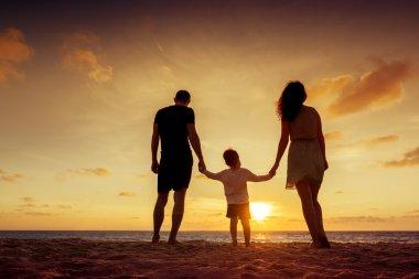 Family standing on sunset