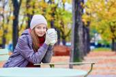 Dívka pití kávy nebo čaje venku