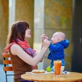 Bella giovane madre con il suo neonato divertendosi insieme nella caffetteria
