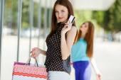 Portrét mladé ženy drží nákupní tašky a kreditní karty