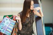 šťastná žena, nakupování a drží tašky v obchoďáku