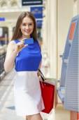 Šťastná bruneta žena výběr peněz z kreditní karty v Atm