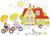 A little girl and a little boy riding bikes on a sunny summer day near a country house