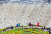 Tourists observes falling wall of water