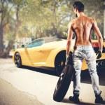 Постер, плакат: Mechanic repairs a luxury car