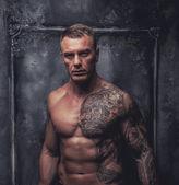 Muskulöse Männer mit Tätowierungen