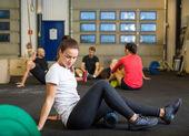 Relaxációs gyakorlat Crossfit edzőteremben csinál nő