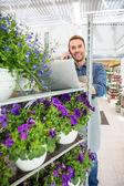 Blumenhändler mit Handy und Laptop im Shop