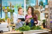 Floristen verwenden digitale Tablet dabei Bouquet im Shop