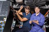 Mechanika s digitálním tabletu pod vyklopeným auto