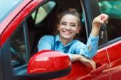 Veselá dívka, sedící v autě s klíči v ruce