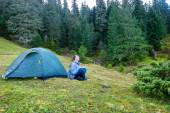 Man practicing yoga near blue camping tent