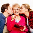 Постер, плакат: Happy family couple with old woman who holding gift box and baby shoe
