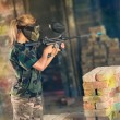 Постер, плакат: Female paintball gamer in action