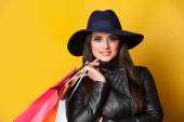 Style brunette girl with bags on yellow background.