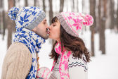 Couple in love kissing in a winter forest in sweaters closeup