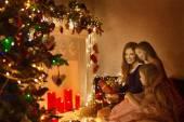Vánoční rodinné žena portrét, matky a dcery oslavit svátek, otevření dárkové krabičce v místnosti zdobí vánoční strom a světla svíček