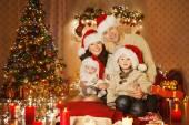 Vánoční rodinný portrét v obýváku domácí dovolené, děti a Baby na čepice Santa s dárkové krabičce, dům, dekorační girlanda svíčky vánoční strom