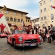 Постер, плакат: A red Mercedes 300 SL W 198 followed by a red Maserati 150 takes part to the 1000 Miglia classic car race