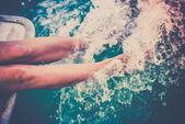 Female legs splashing sea water