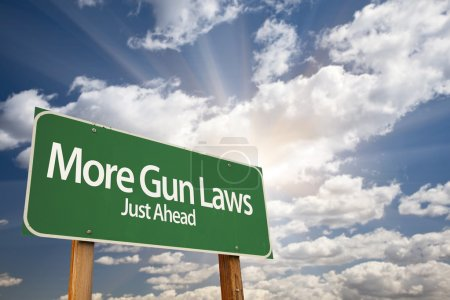 Постер, плакат: More Gun Laws Green Road Sign Over Clouds, холст на подрамнике