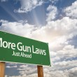 Постер, плакат: More Gun Laws Green Road Sign Over Clouds