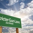 Постер, плакат: Stricter Gun Laws Green Road Sign Over Clouds