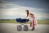 Woman walking through the countryside with a cart aul of baby