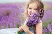 Glückliche kleine Mädchen im Lavendelfeld mit Blumenstrauß