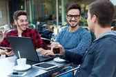 Venkovní portrét mladých podnikatelů na kavárnu