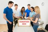 Emberek keresnek adomány dobozban