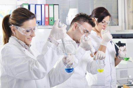 Постер, плакат: Attractive young PhD students scientists observing in the labora, холст на подрамнике