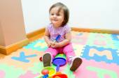 Adorable baby girl playing on floor mats