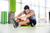 Člověk dělá protahovací cvičení v tělocvičně