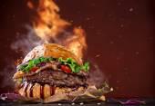 Deliziosi hamburger con fiamme di fuoco su fondo in legno