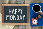 Happy Monday sign on blackboard with cup of coffee biscuits and clock on wooden background