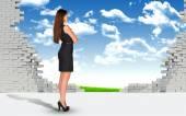 Geschäftsfrau und zerstörten Ziegelmauer mit Naturlandschaft