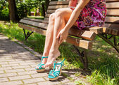 Woman stroking her leg while sitting on a park bench